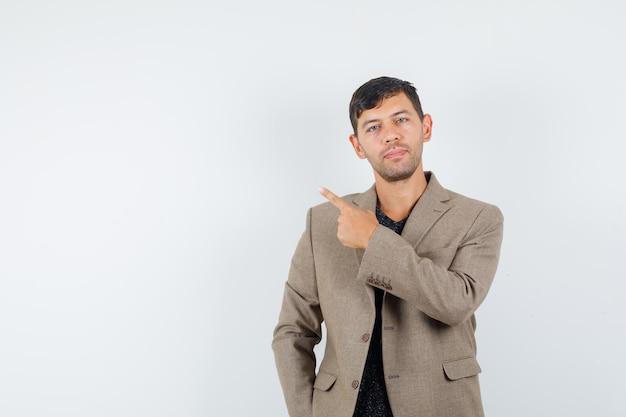 若い男性は灰色がかった茶色のジャケットで後ろを指して、焦点を合わせて、正面図を探しています。テキスト用のスペース