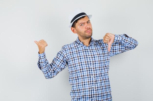 Молодой мужчина указывает назад, показывая большой палец вниз в клетчатой рубашке