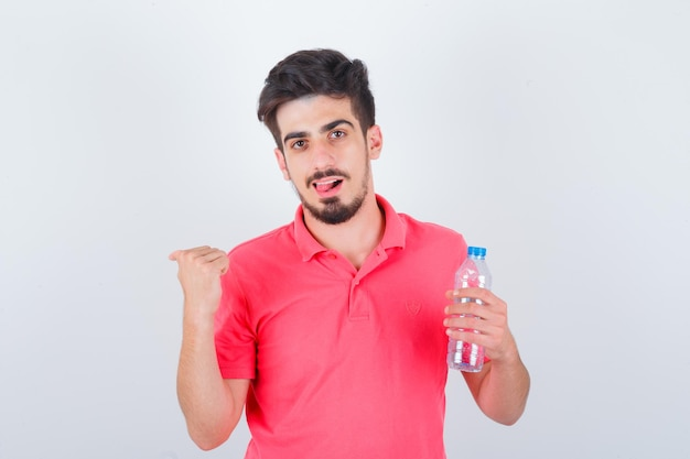 Tシャツで舌を突き出し、幸せそうに見える、正面図を親指で後ろを指す若い男性。