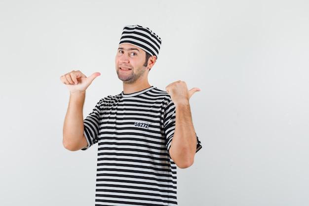 젊은 남성 t- 셔츠, 모자에 엄지 손가락으로 다시 가리키는 자신감, 전면보기를 찾고.
