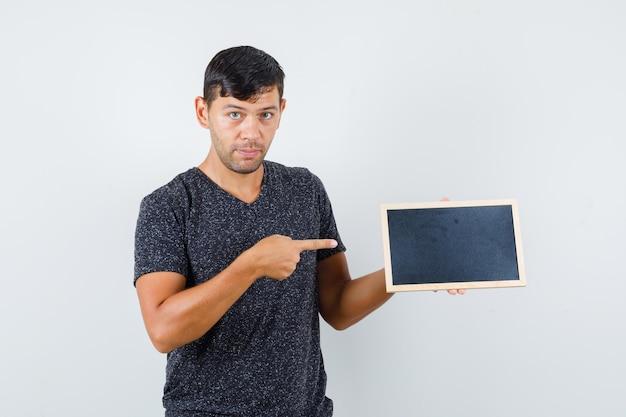 Giovane maschio che indica cartone nero in maglietta nera e sembra sicuro. vista frontale.