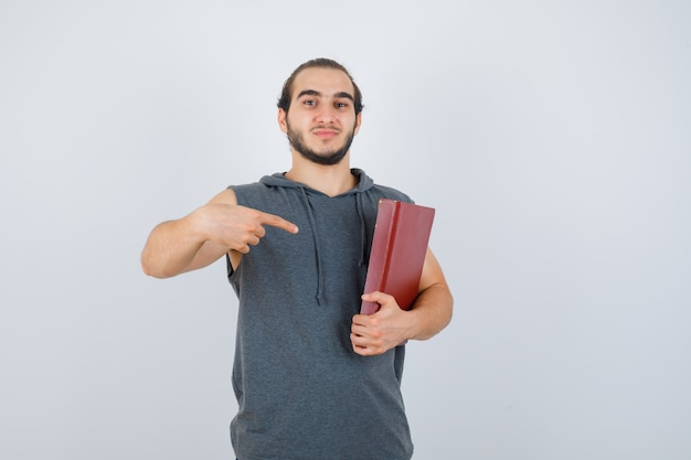 Young male pointing at book in sleeveless hoodie and looking confident , front view.