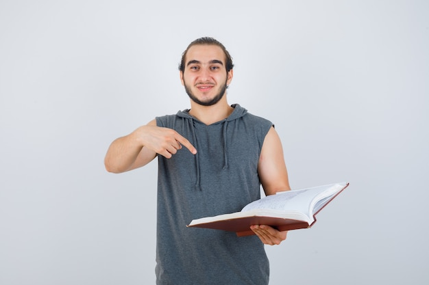 Young male pointing at book in sleeveless hoodie and looking pretty , front view.