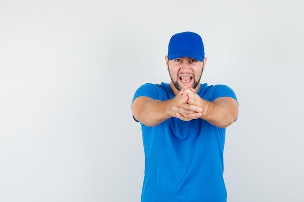 Молодой мужчина в синей футболке и кепке показывает жестом пистолета и выглядит разгневанным