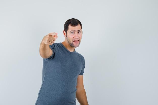 Giovane maschio che indica alla macchina fotografica in maglietta grigia e che sembra fiducioso