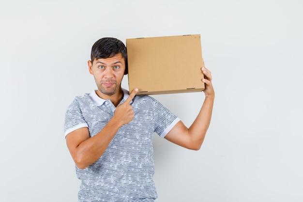 Giovane maschio che indica alla scatola di cartone in maglietta e che sembra allegro