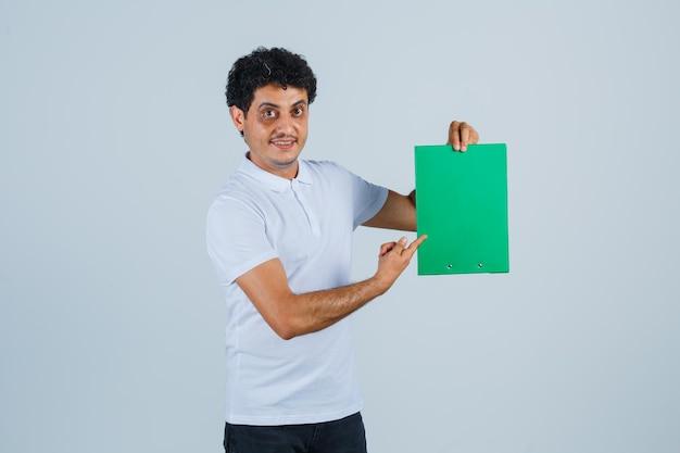 Giovane maschio che indica alla lavagna per appunti in maglietta bianca, pantaloni e guardando allegro, vista frontale.