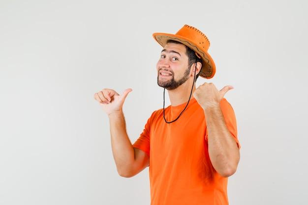주황색 티셔츠, 모자를 쓰고 즐거운 표정으로 두 개의 엄지손가락을 옆으로 가리키는 젊은 남성. 전면보기.