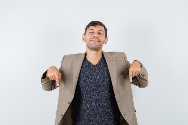 Giovane maschio che punta verso il basso in giacca marrone grigiastra, camicia nera e sguardo fiducioso, vista frontale.
