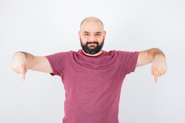 ピンクのtシャツを着て下を向いて喜んでいる若い男性。正面図。