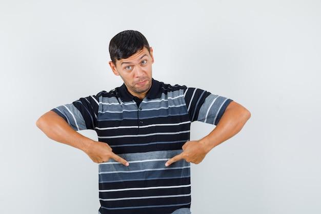 Молодой мужчина, указывая вниз в вопросительном жесте в футболке, вид спереди.