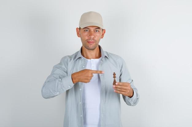 Молодой мужчина показывает пальцем на шахматную фигуру в рубашке и кепке и выглядит позитивно