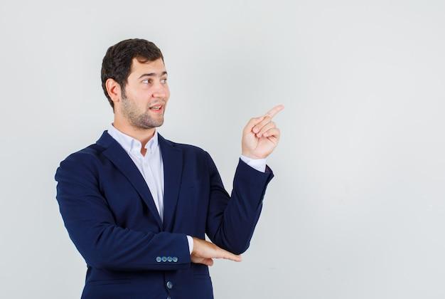 Giovane maschio puntare il dito lontano in tuta e guardando felice. vista frontale.