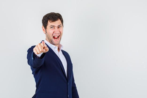 Giovane maschio puntare il dito gridando in tuta e guardando nervoso. vista frontale.