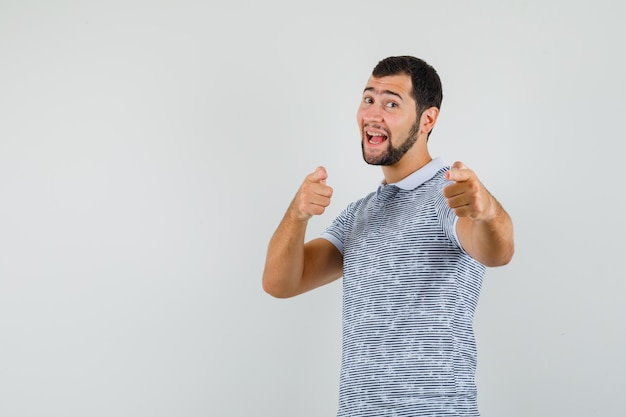Young male pointing finger pistols in t-shirt and looking amused , front view.
