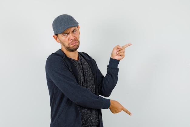 Giovane maschio che punta le dita su e giù in t-shirt, giacca, berretto e sembra indeciso. vista frontale.
