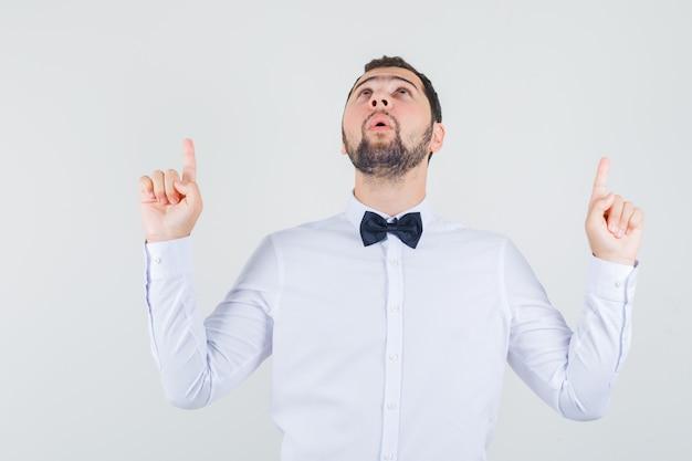 若い男性は白いシャツを着て指を上に向け、感謝しているように見えます。正面図。
