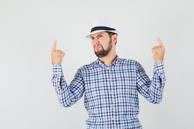 Giovane maschio che punta le dita verso l'alto mentre accigliato in camicia a quadri