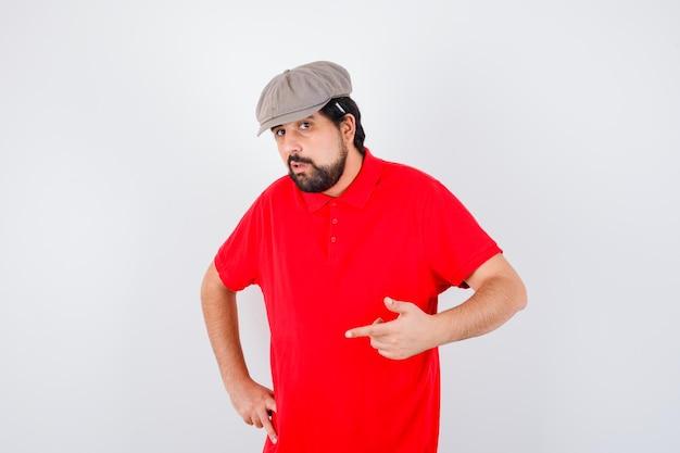 赤いtシャツ、キャップで前を向いて自信を持って見える若い男性。正面図。