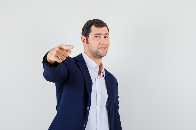 Young male pointing at front in shirt and jacket and looking confident