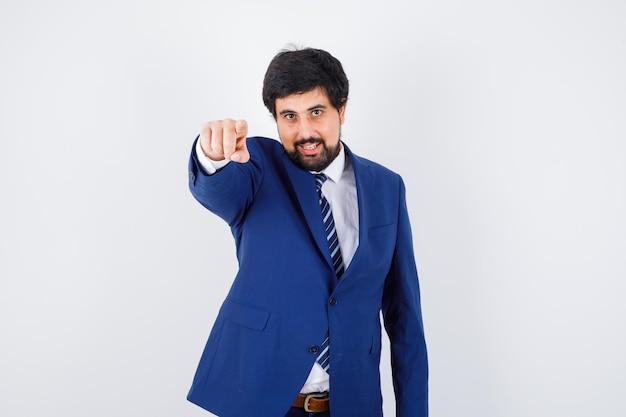 Giovane maschio che indica davanti in camicia, giacca, cravatta, vista frontale.