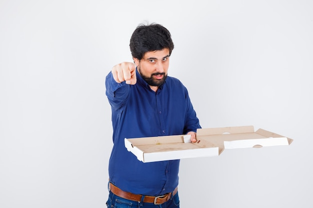 Young male pointing at front while holding pizza box in shirt, jeans and looking confident , front view.