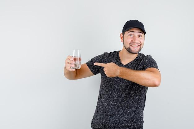 Giovane maschio che indica al bicchiere d'acqua in maglietta e berretto e sembra allegro