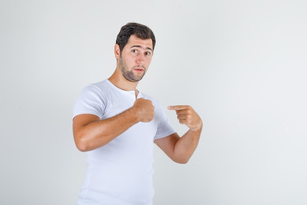 Young male pointing at himself and asking 'me?' in white t-shirt , front view.