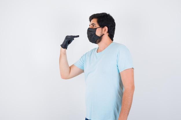 Молодой мужчина, указывая на себя в футболке и глядя сосредоточенно, вид спереди.