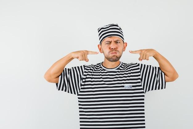 Giovane maschio che indica alle sue guance soffiate in cappello della maglietta a strisce e che sembra cupo