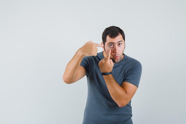 Giovane maschio che indica alla sua palpebra tirato dal dito in maglietta grigia