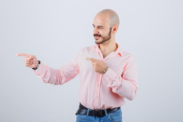 Giovane maschio che indica il lato sinistro in camicia, jeans e sembra sicuro. vista frontale.