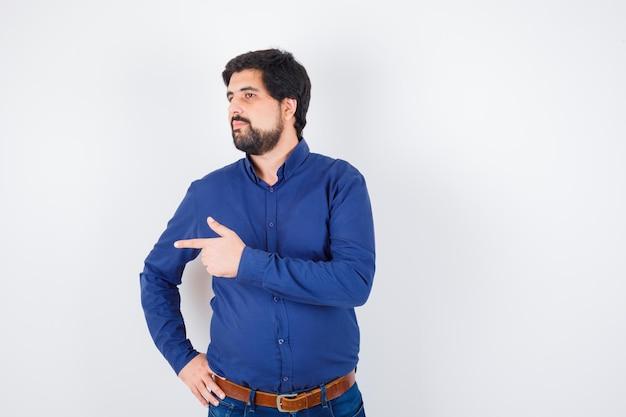 Giovane maschio che indica il lato sinistro in camicia, jeans e sembra concentrato. vista frontale.