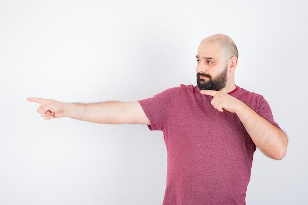 Giovane maschio che indica il lato sinistro in t-shirt e sembra carino, vista frontale.