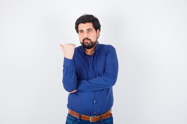Giovane maschio che indica il lato sinistro con il pollice in camicia, jeans e guardando fiducioso, vista frontale.