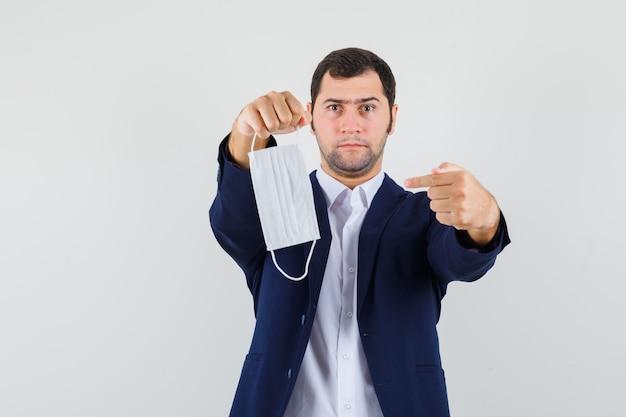 Giovane maschio che punta alla mascherina medica in camicia