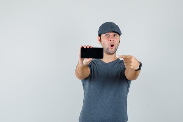 Giovane maschio che indica al telefono cellulare in protezione della maglietta e che sembra stupito