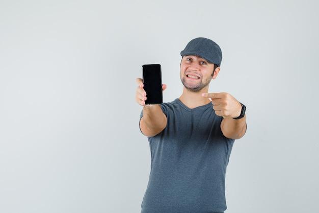 Giovane maschio che indica al telefono cellulare in protezione della maglietta e che sembra contento
