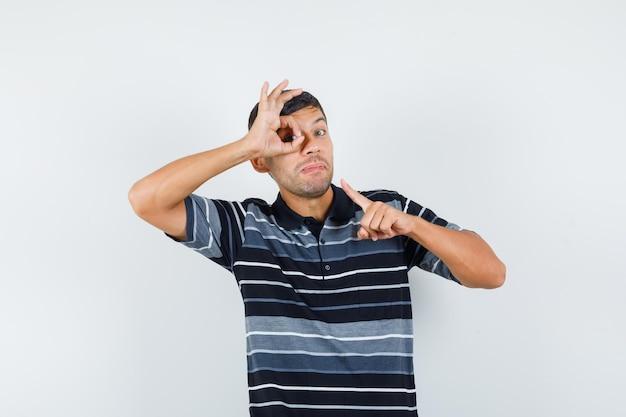 Giovane maschio che indica il segno giusto sul suo occhio in maglietta e sembra sicuro. vista frontale.