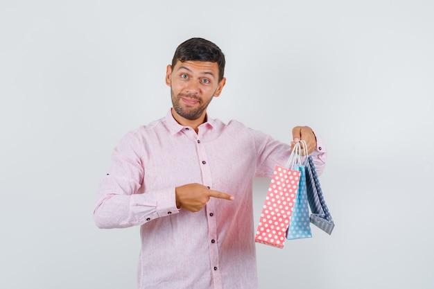 Giovane maschio che punta a sacchetti di carta in camicia e che sembra felice. vista frontale.