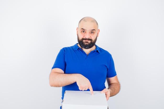 젊은 남성이 티셔츠를 입고 피자 상자를 가리키며 즐거운 표정을 짓고 있습니다.