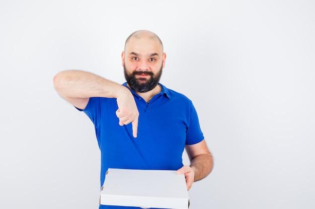 젊은 남성이 티셔츠를 입고 피자 상자를 가리키고 즐거워 보입니다. 전면보기.