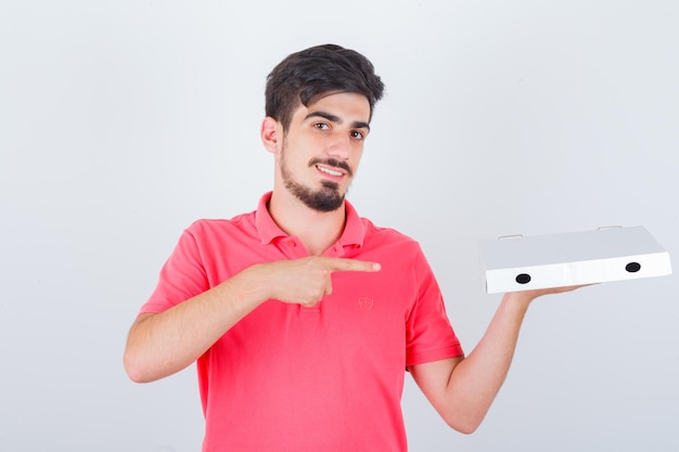 Young male pointing pizza box in t-shirt and looking joyful , front view.