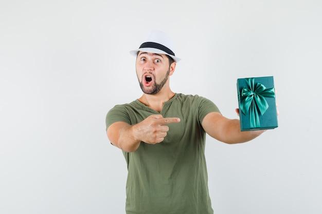 Giovane maschio che punta alla casella attuale in maglietta verde, cappello e sguardo stupito