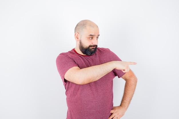 Giovane maschio che indica il lato destro in maglietta e sembra interrogato. vista frontale.