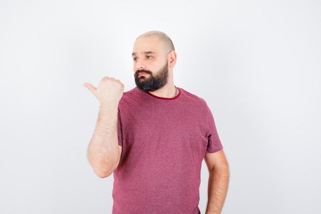 Giovane maschio che indica il lato destro con il pollice in maglietta e sembra esitante, vista frontale.