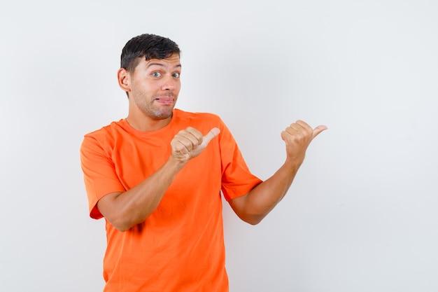 オレンジ色のtシャツに親指を向けて気づいている若い男性