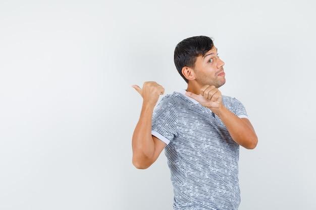 Молодой мужчина показывает большими пальцами обратно в футболке и выглядит веселым