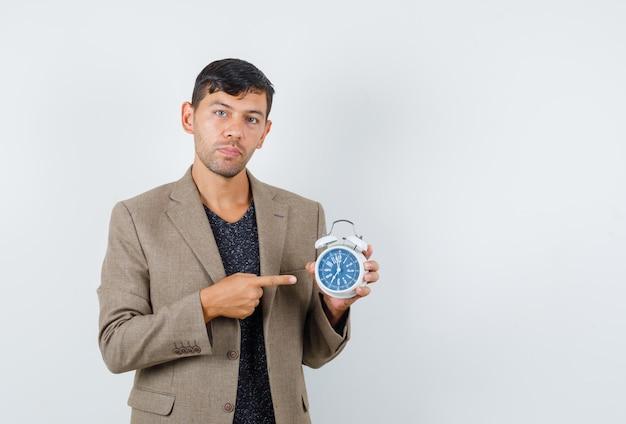 灰色がかった茶色のジャケットで時計を指して、焦点を合わせて、正面図を探している若い男性。テキスト用のスペース