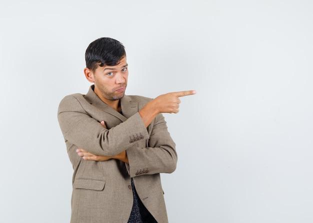若い男性は灰色がかった茶色のジャケット、黒のシャツで横を指して、焦点を合わせて、正面図を探しています。テキスト用のスペース
